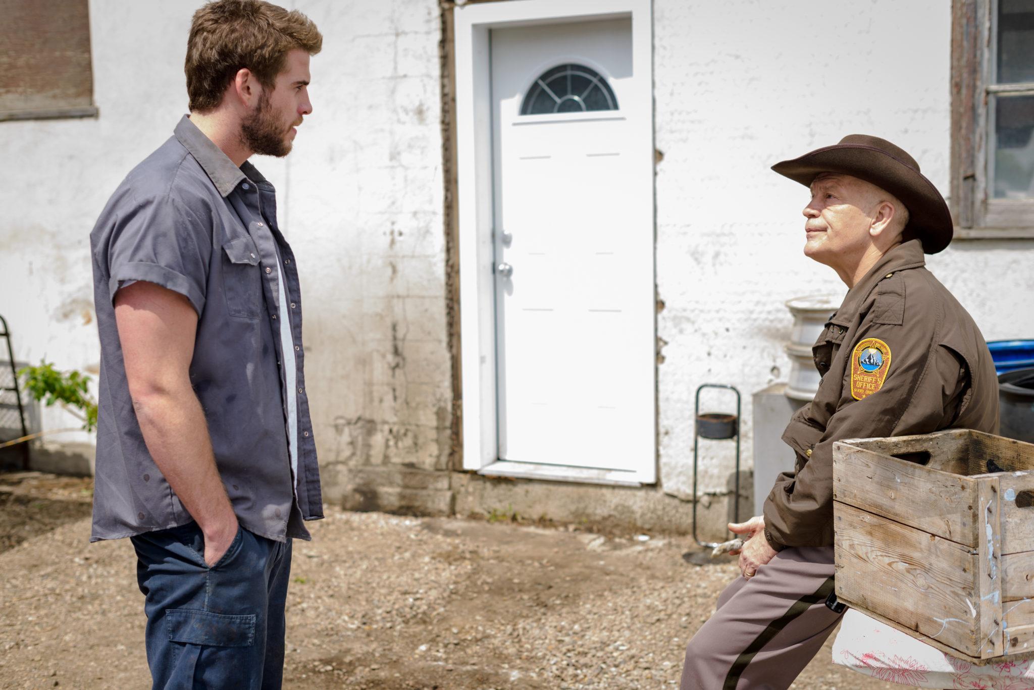 """Dwayne und Sheriff Vogel stecken den Mord unterschiedlich gut weg (Liam Hemsworth und John Malkovich in """"Cut Bank"""", Foto: Koch Media)"""